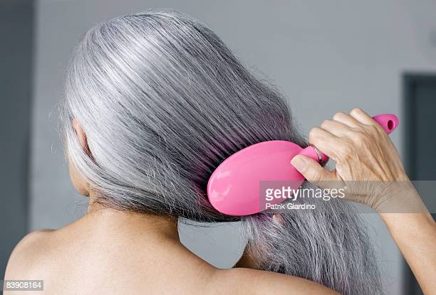 Mature woman with hair brush