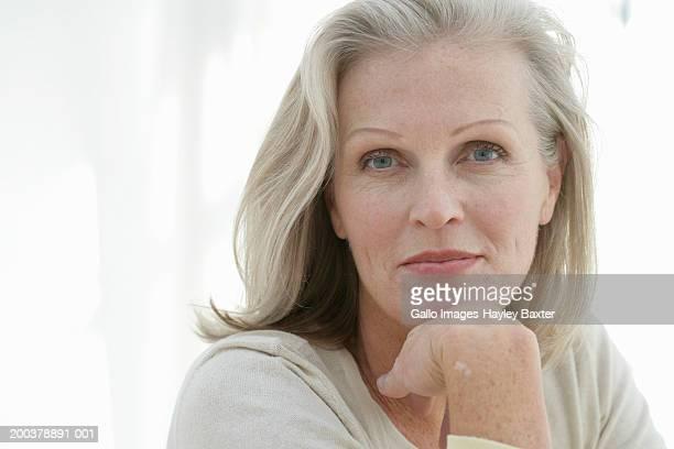 mature woman with hand to chin, close-up, portrait - melena mediana fotografías e imágenes de stock