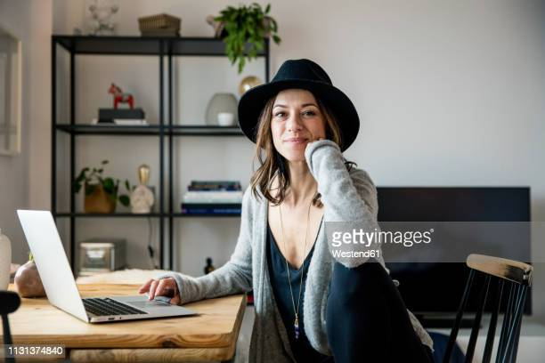 mature woman with hat, sitting at home, using laptop - influencer stock pictures, royalty-free photos & images