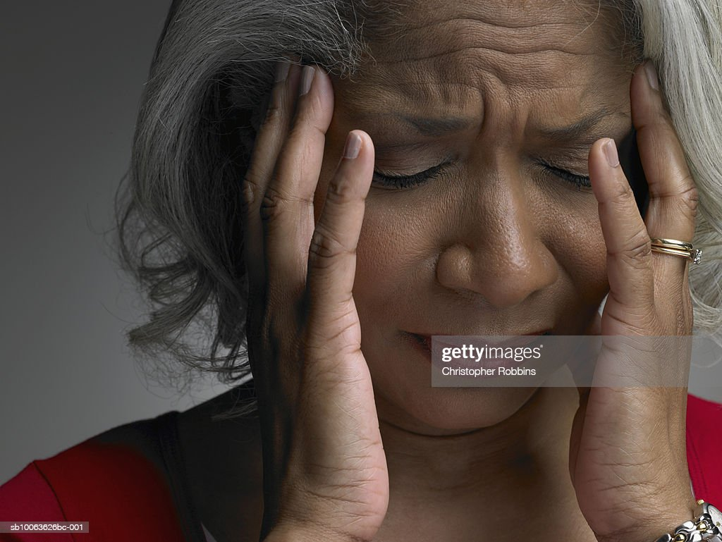 Mature woman with head in hands and eyes closed, close-up : Stock Photo