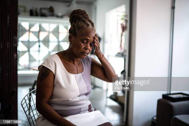 mature woman with headache at home - fragility stock pictures, royalty-free photos & images