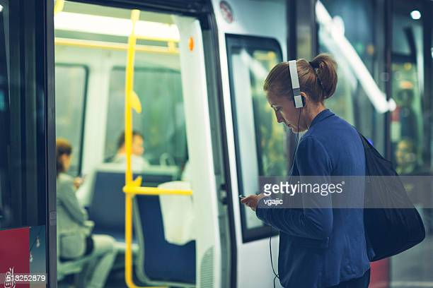 Mature Woman With Headphones at subway station.