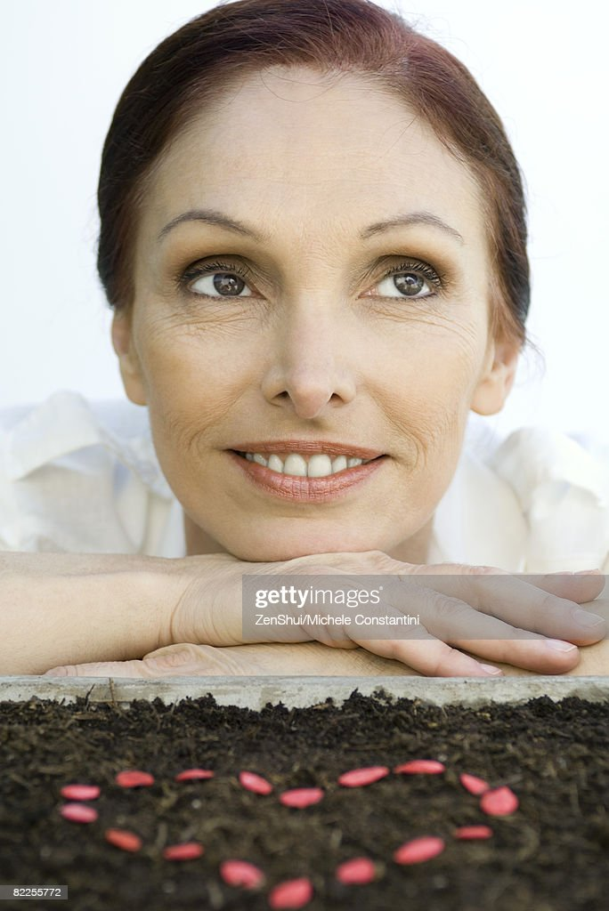 Mature woman with heart shape made of seeds on soil : Stock Photo