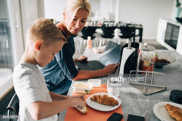 Mature woman with laptop looking at son applying butter on croissant in kitchen