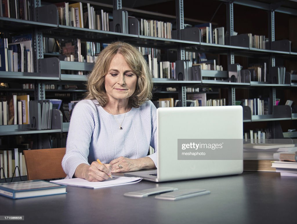 Mature Woman With Laptop Working On Something : Stock Photo