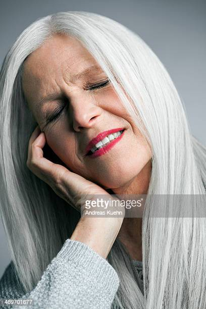 Mature woman with long grey hair and eyes closed.