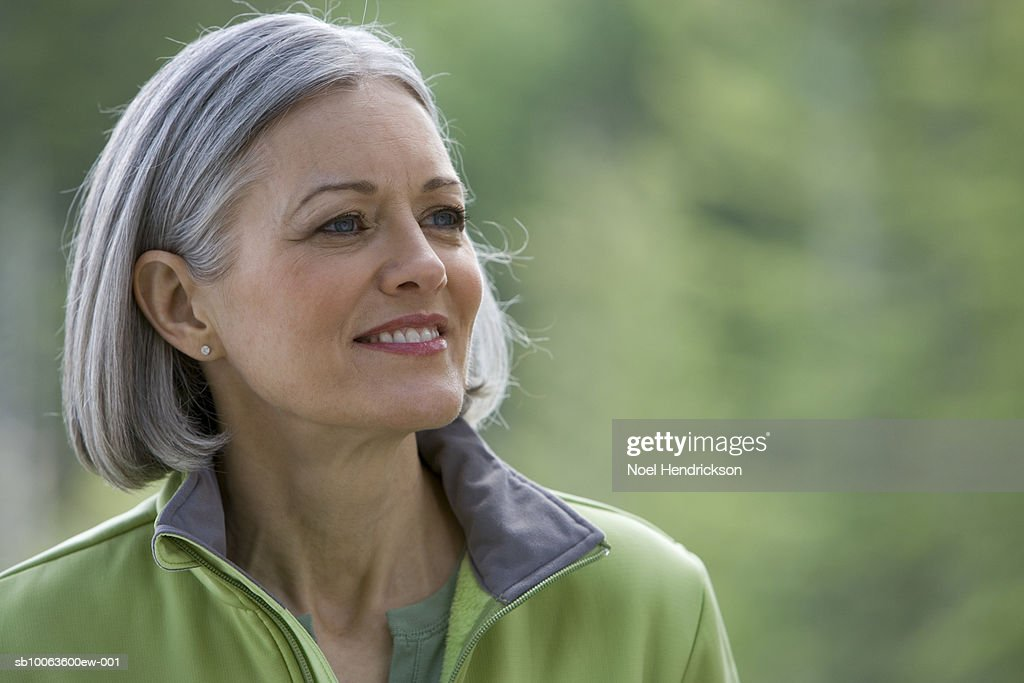 Mature woman with long grey hair looking aside, close-up : Stock Photo