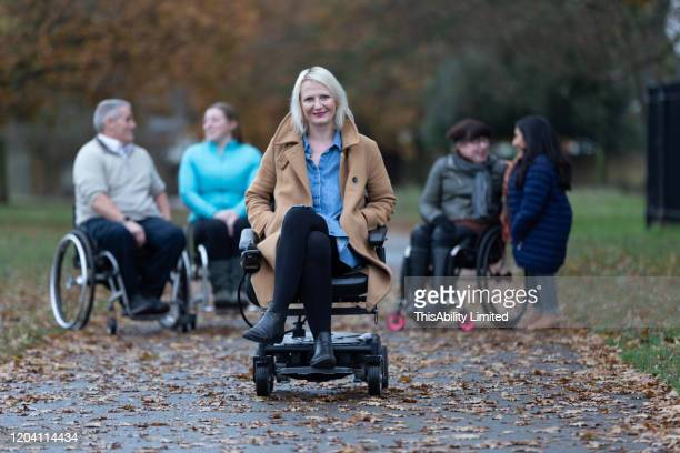 mature woman with lyme disease sitting in wheelchair in park - disabilitycollection stock pictures, royalty-free photos & images