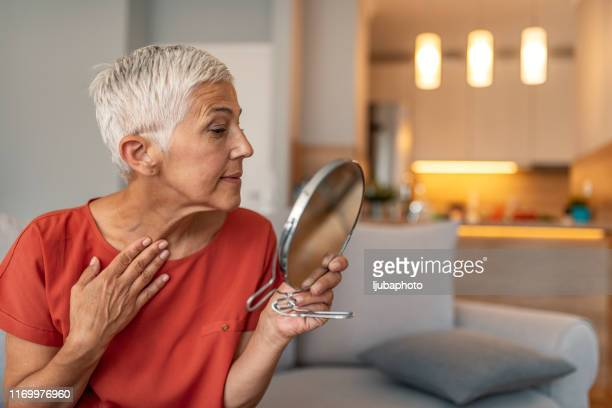 mature woman with make-up mirror massaging her face and neck - anthropomorphic face stock pictures, royalty-free photos & images