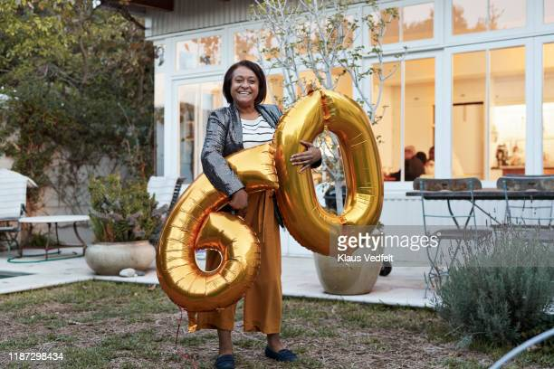 mature woman with number 60 balloons in backyard - woman birthday stock pictures, royalty-free photos & images