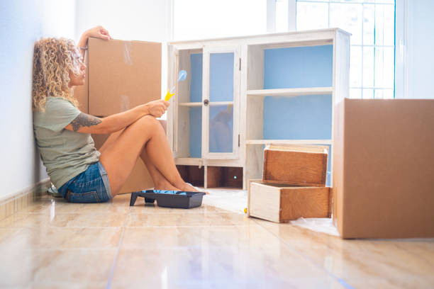 Mature woman with paint roller looking at cabinet while sitting by cardboard box