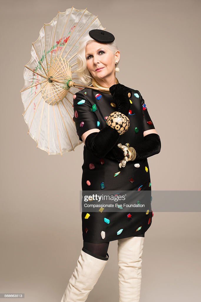 Mature woman with parasol and stylish clothes : Stock Photo