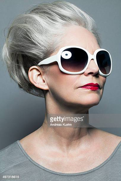Mature woman with red lipstick and sunglasses.