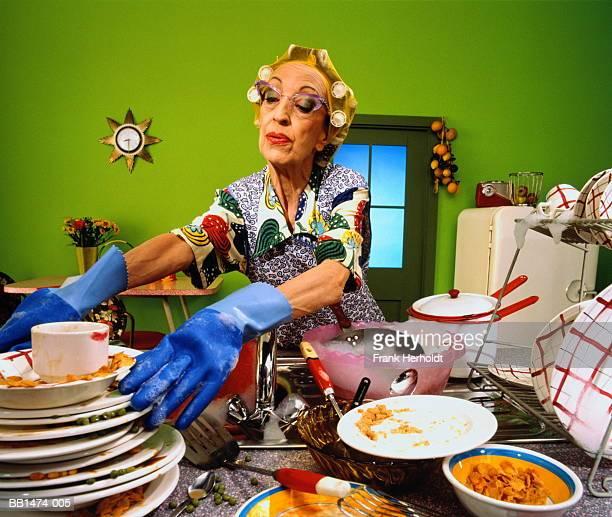 mature woman with rollers in hair, stacking dirty dishes - krulspelden stockfoto's en -beelden