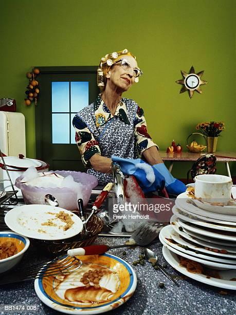mature woman with rollers in hair, washing up dirty dishes - unterschicht stereotypen stock-fotos und bilder