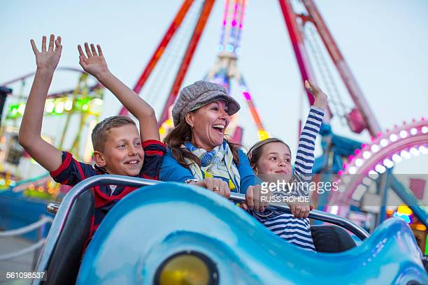 mature woman with son and daughter on fairground ride - amusement park ride stock pictures, royalty-free photos & images