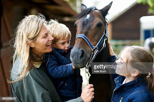 mature woman with son and daughter petting horse - horseback riding stock pictures, royalty-free photos & images