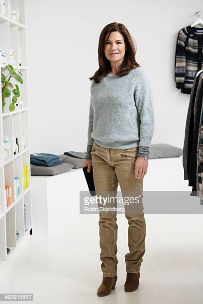 Mature woman with Ipad in clothing store
