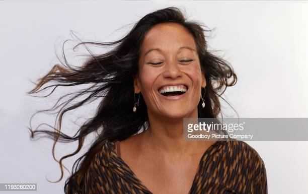 mature woman with tousled hair laughing against a gray background - grey dress stock pictures, royalty-free photos & images