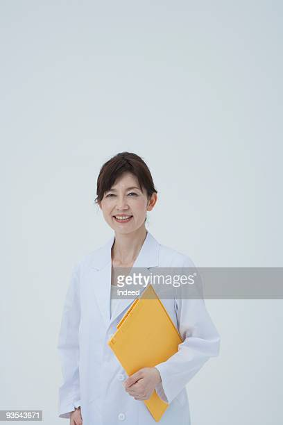 Mature woman with white coat hodling file, smiling