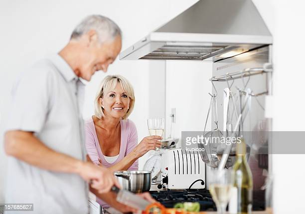 Ältere Frau mit Wein Glas und blur man bereitet Speisen