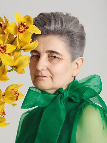 Mature woman with yellow orchid - gettyimageskorea