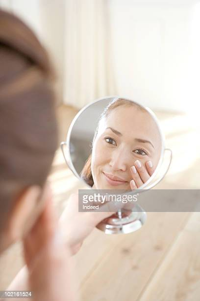 mature woman woman looking in hand held mirror - vanity mirror stock pictures, royalty-free photos & images