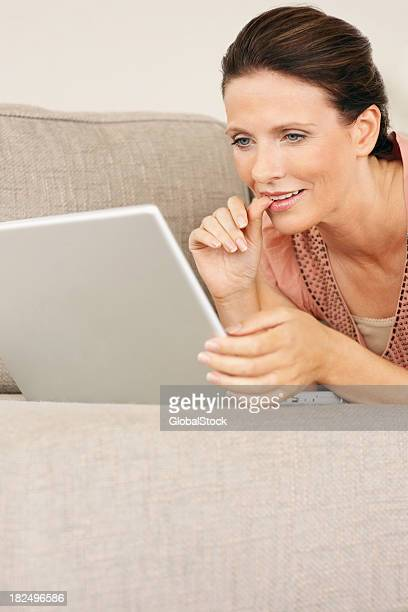 Mature woman working a laptop while lying on couch