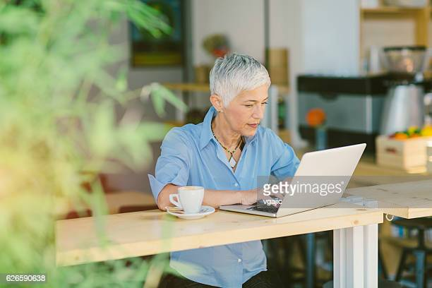 Mature Woman Working And Drinking Coffee In Local Cafe.