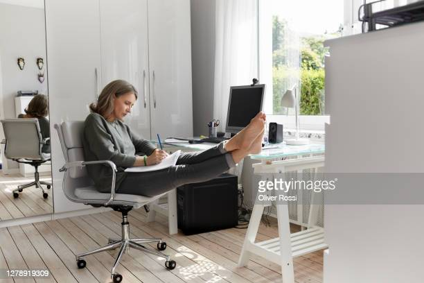 mature woman working at desk at home taking notes - chair stock pictures, royalty-free photos & images