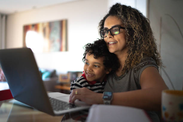 mulher madura trabalhando em casa, carregando filho jovem - children internet - fotografias e filmes do acervo