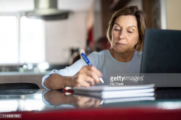 mature woman working at home - corsi educativi per adulti foto e immagini stock