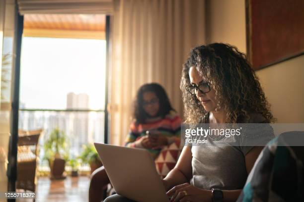 mature woman working at home, using laptop sitting on the couch - routine stock pictures, royalty-free photos & images
