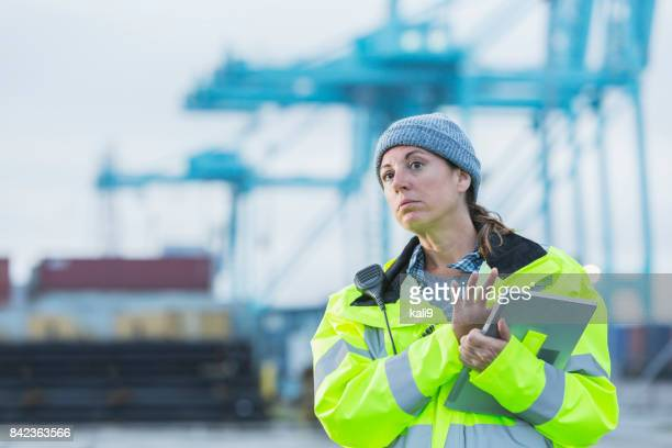 Mature woman working at shipping port, digital tablet