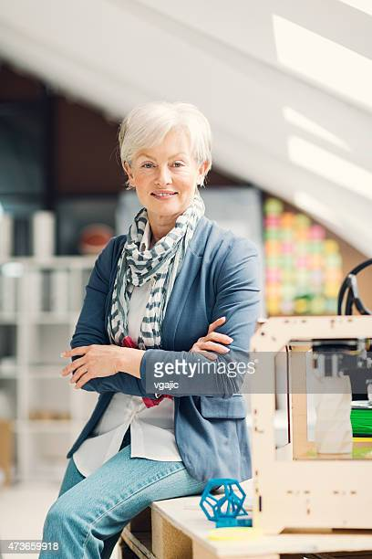 Mature Woman Working By 3D Printer in New Startup Office.