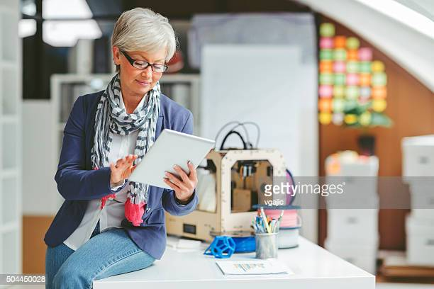 Mature Woman Working By 3D Printer