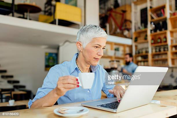 Mature Woman Working Drinking Coffee In Local Cafe.