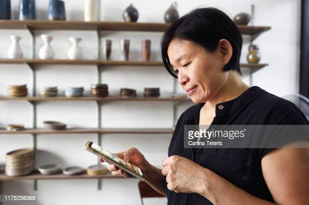mature woman working from her mobile phone in her art shop - シンガポール文化 ストックフォトと画像