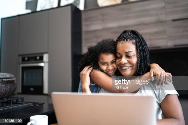 reife frau arbeitet von zu hause aus und wird von tochter umarmt - mother daughter webcam stock-fotos und bilder