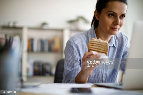 mujer madura trabajando desde casa - lunch fotografías e imágenes de stock