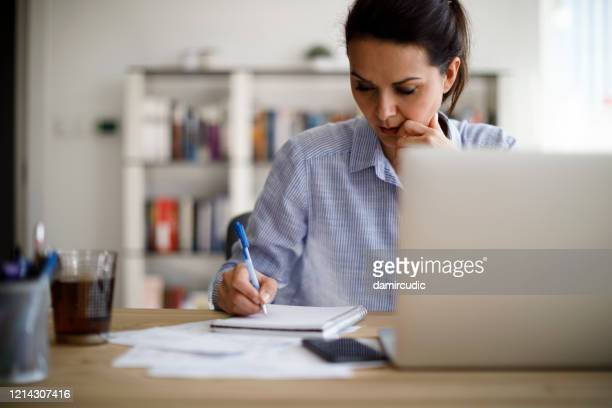 mature woman working from home - concentration stock pictures, royalty-free photos & images