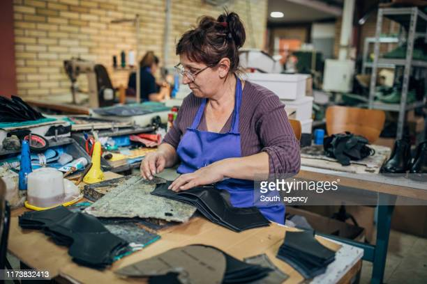 mature woman working hard at shoe factory - shoe factory stock pictures, royalty-free photos & images