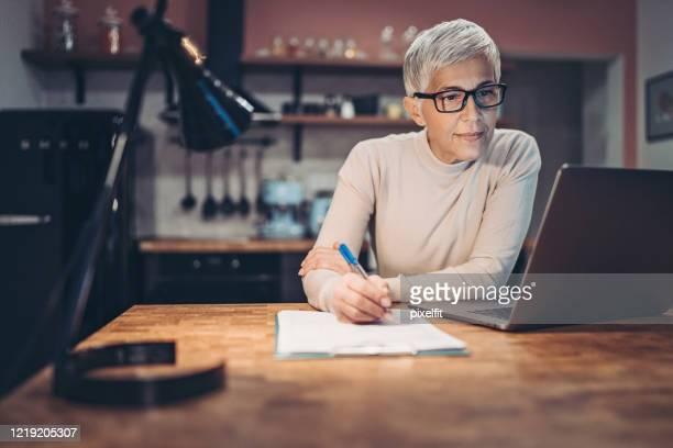 夜に家庭の台所で働く成熟した女性 - 金融関係の職業 ストックフォトと画像