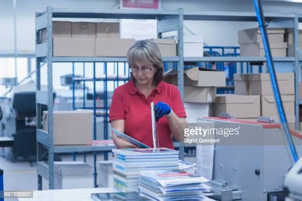 mature woman working in books printing industry, bremgarten, hartheim am rhein, baden-wuerttemberg, germany - sigrid gombert imagens e fotografias de stock
