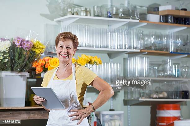 mature woman working in flower shop using digital tablet - kali rose stock pictures, royalty-free photos & images