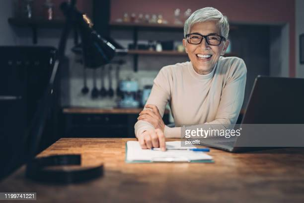 mature woman working late from home - authors stock pictures, royalty-free photos & images