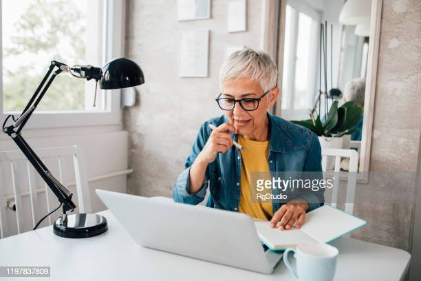 mature woman working online - business plan stock pictures, royalty-free photos & images