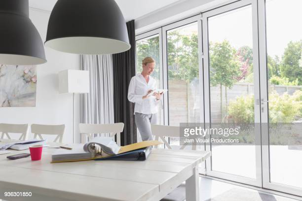 Mature woman working with mobile devices in modern living room