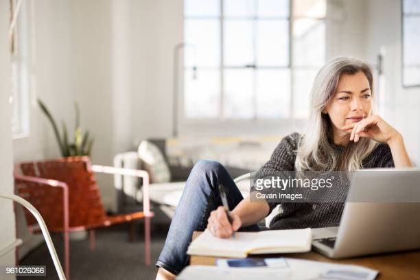 mature woman writing in diary while working at home - mulheres maduras imagens e fotografias de stock