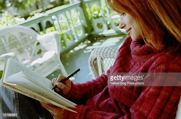 mature woman writing in journal on porch - dog pad foto e immagini stock